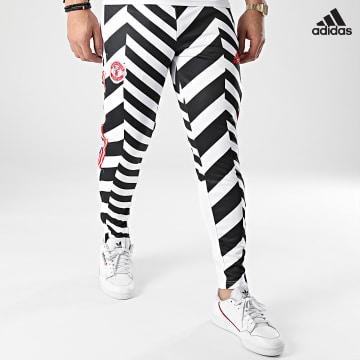 https://laboutiqueofficielle-res.cloudinary.com/image/upload/v1627638668/Desc/Watermark/adidas_performance.svg Adidas Performance - Pantalon Jogging A Bandes Manchester United FC AOP GK9435 Blanc Noir